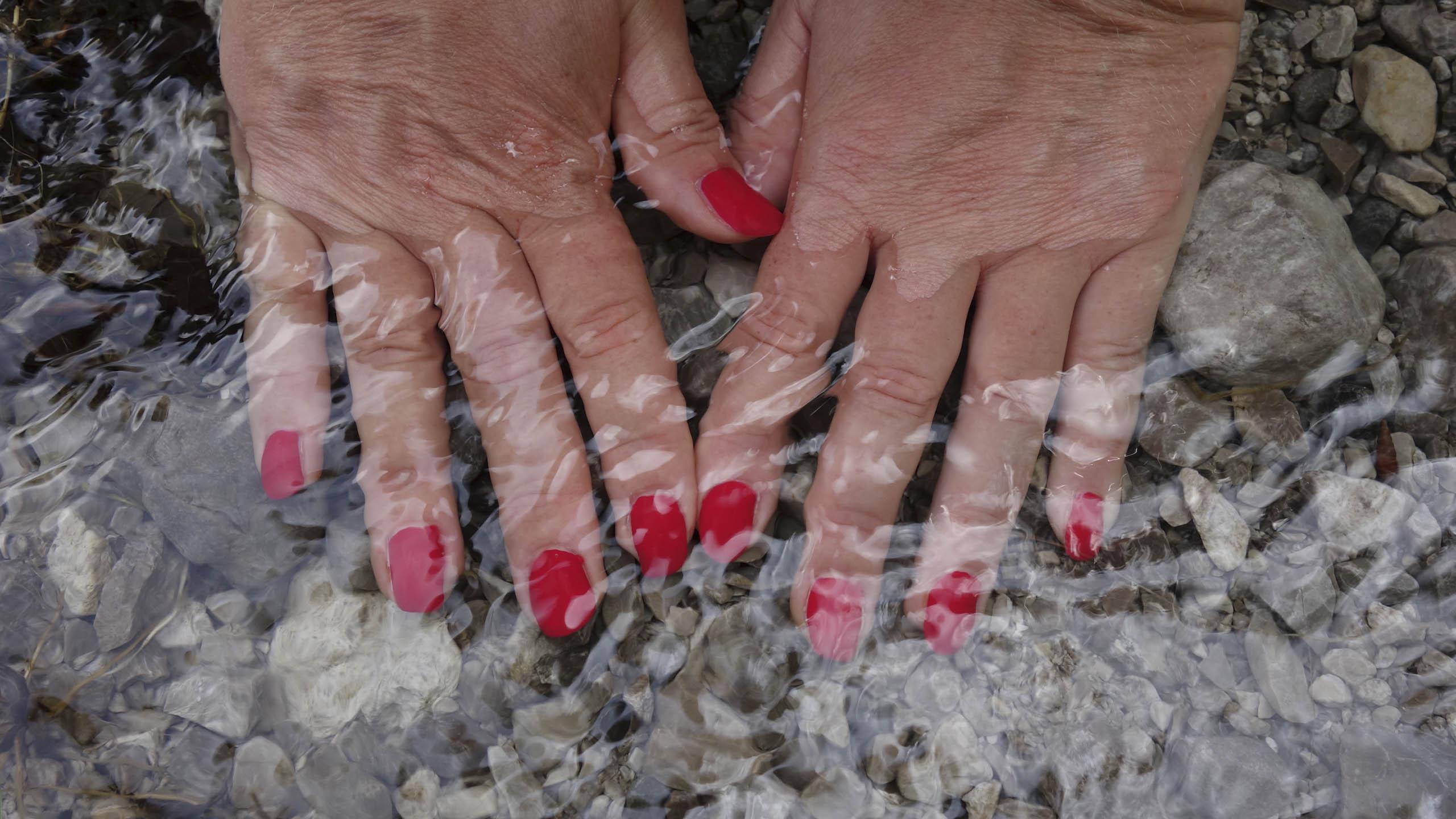 Frauenhände fühlen fisches Wasser